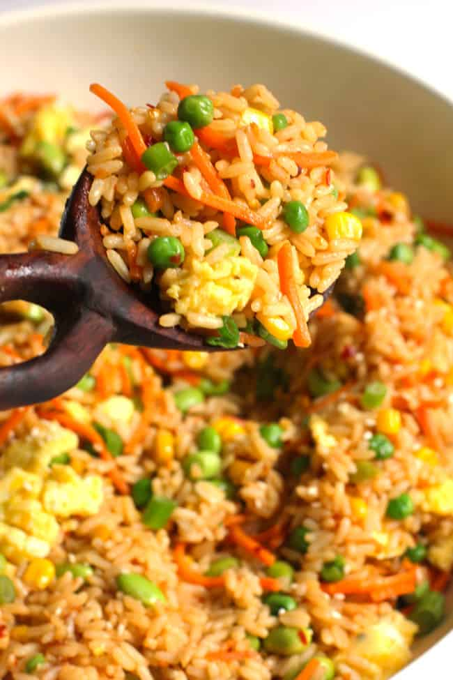 Close-up shot of a spoonful of spicy fried rice in a large white bowl of spicy fried rice.