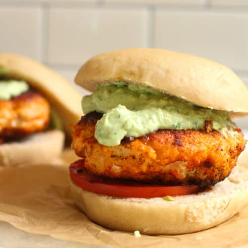 Side shot of a blackened salmon burger with Avocado Crema, on a wheat bun with a white background.