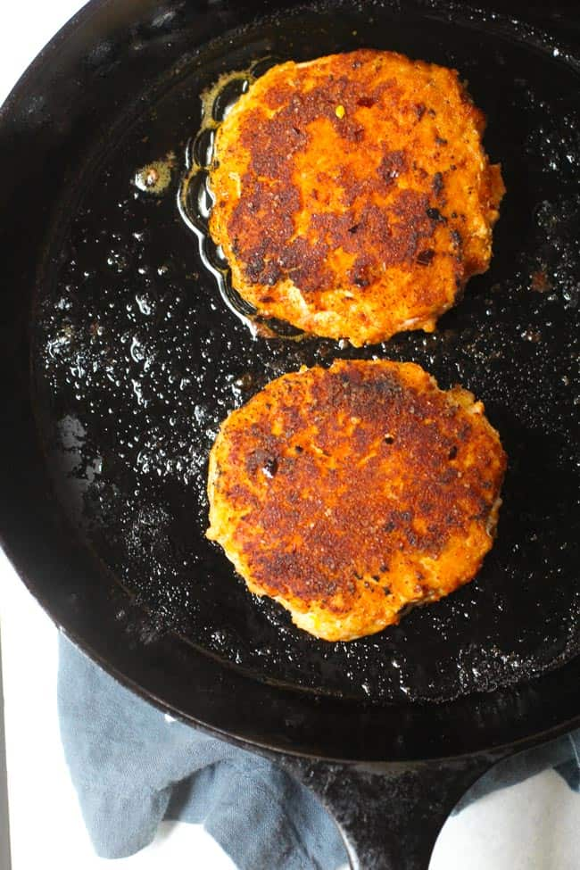 Overhead shot of cooked blackened salmon burgers in a cast iron skillet.