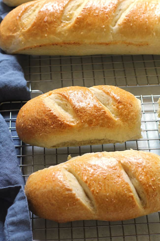 Side shot of two smaller hoagie buns of French bread, with a larger one in the background.