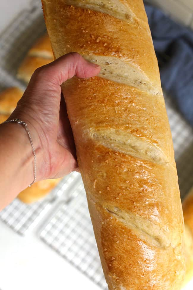 My hand holding a large loaf of Chewy French bread.