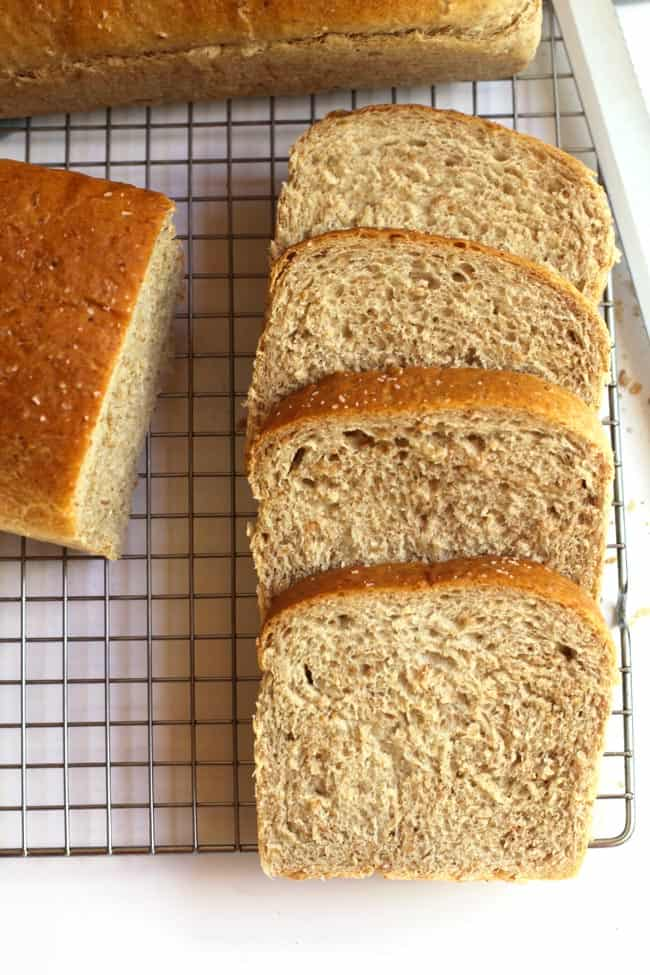 Overhead shot of the sliced cracked wheat bread, next to loafs of entire loafs.