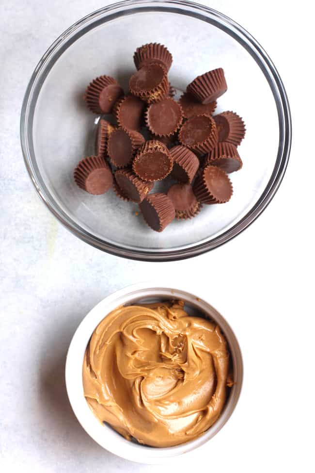 Overhead shot of a bowl of peanut butter cups and another small bowl of creamy peanut butter.