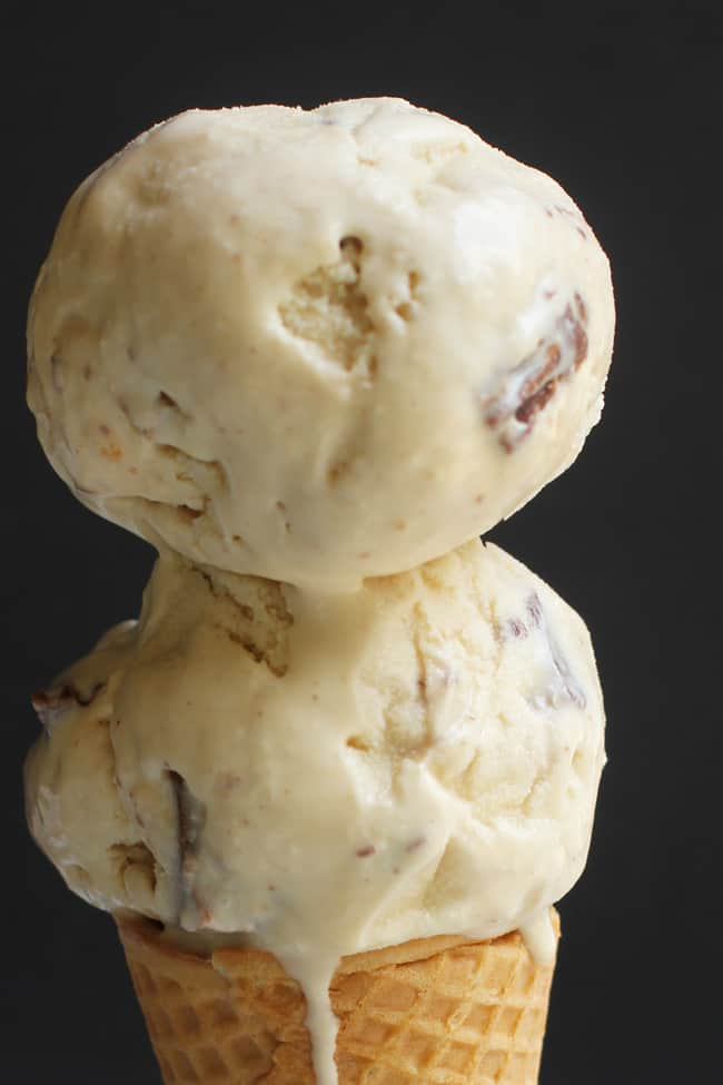 Close-up shot of a creamy peanut butter double ice cream cone, with some drips melting off, with a black background.