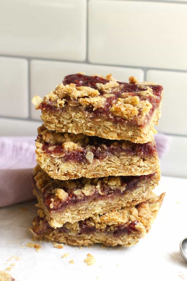 Side shot of four stacked Oatmeal Raspberry Jam Bars, on some white parchment paper, with a purple napkin..