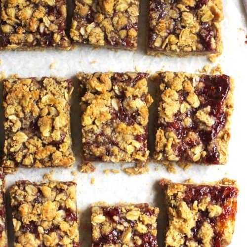 Overhead shot of 9 Oatmeal Raspberry Jam Bars, on some white parchment paper.