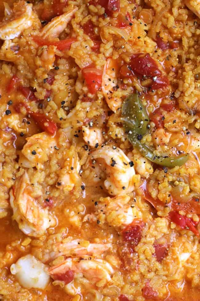 Close-up shot of Spanish Seafood Paella, showing the shrimp, peppers, and rice.