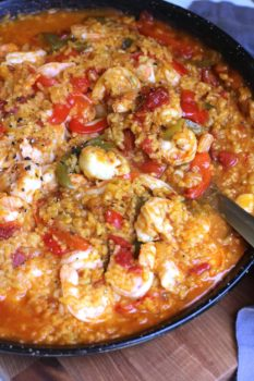Overhead shot of Spanish Seafood Paella, in a large flat paella pan, with a large serving spoon scooping.
