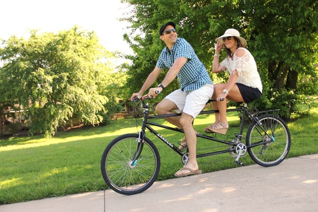 Mike and Sue riding a tandem bike in a park in Texas.