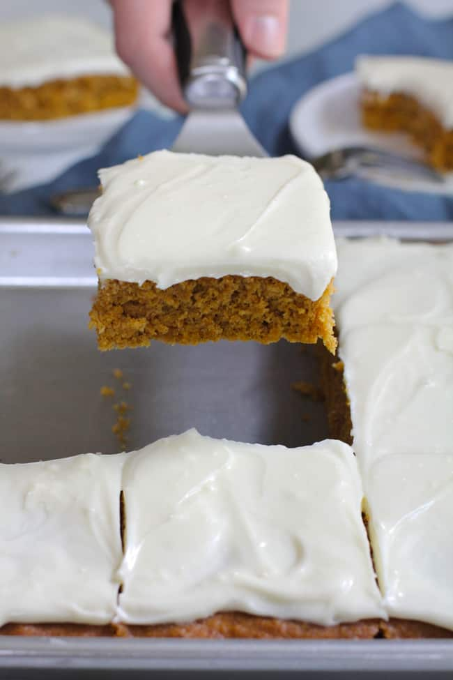 Side shot of a hand using a spatula to lift a piece of pumpkin cake from a pan, with a blue napkin in the background.
