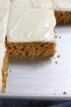 Side shot of a partial pan of pumpkin cake with cream cheese frosting, showing the moist cake layer.