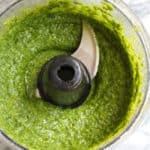 Overhead shot of homemade basil pesto sauce in a food processor.