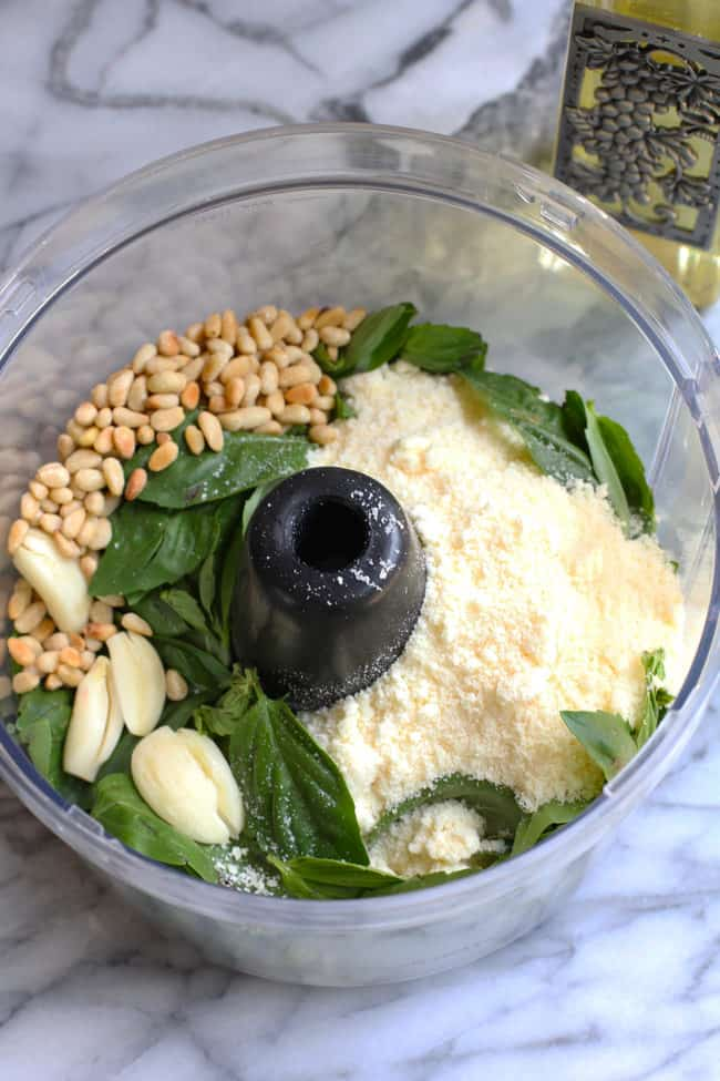 Overhead shot of basil pesto sauce ingredients in a food processor.