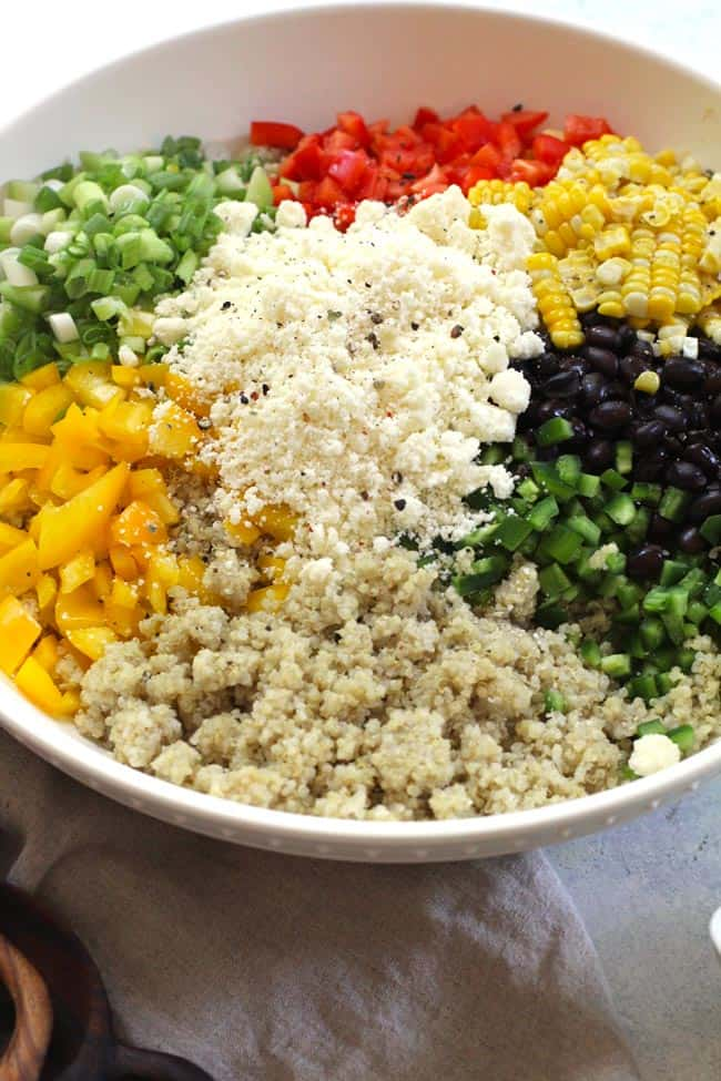 A large white bowl of quinoa salad separated out by ingredient.