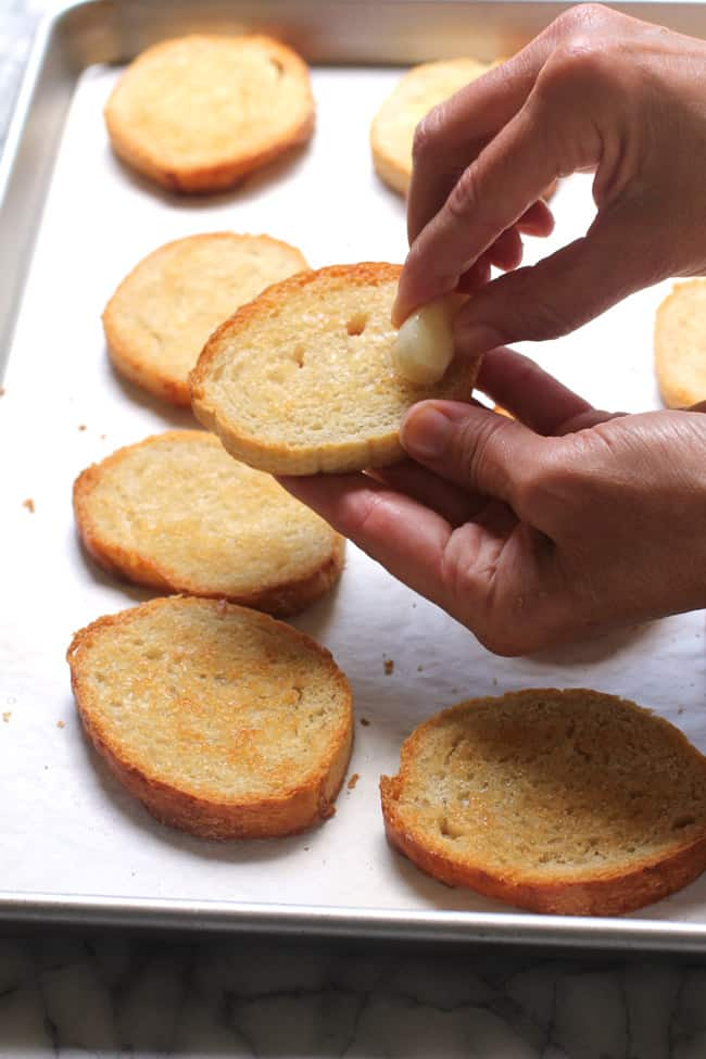 Side shot of my hands rubbing garlic on some toasted bread.