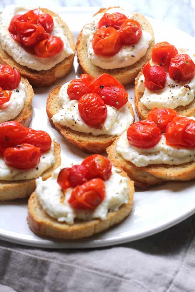 Overhead shot of roasted tomato bruschetta with ricotta, on a white platter.