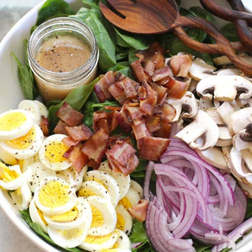 Overhead shot of a large white bowl of spinach salad ingredients in sections, with a jar of Honey Dijon dressing.