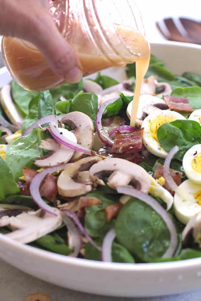 Side shot of my hand pouring Honey Dijon dressing on a large bowl of fresh spinach salad with eggs, bacon, red onion, and mushrooms.