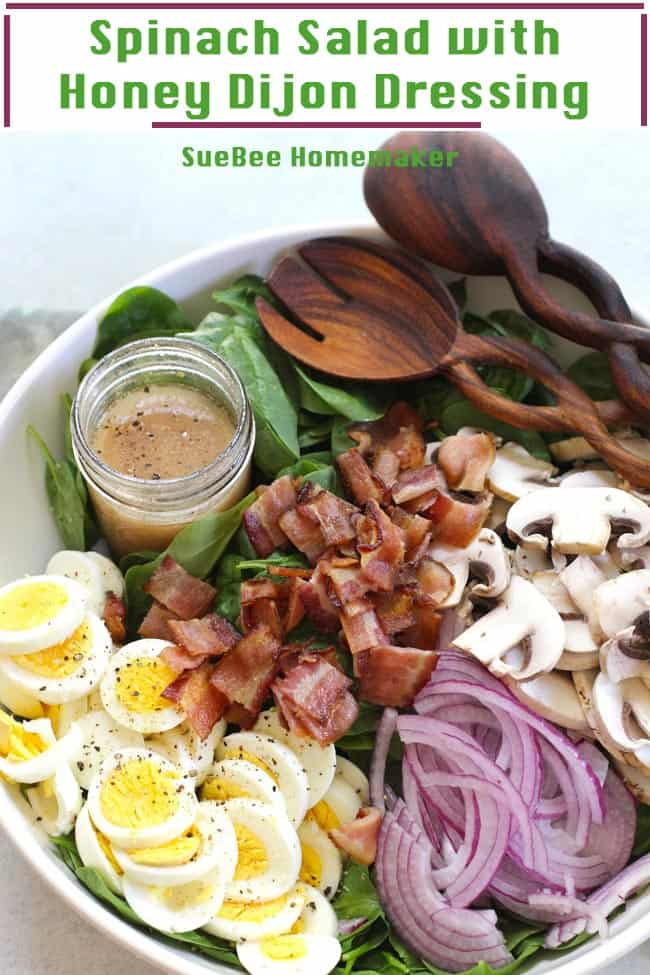 A large white bowl with spinach salad - eggs, bacon, mushrooms, red onions, Honey Dijon dressing, with wooden spoons.