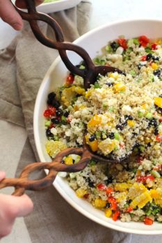 Overhead shot of half of a large white bowl of Mexican Quinoa Salad, with two wooden spoons scooping some up.