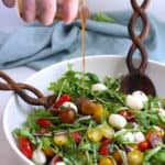 Side shot of a hand drizzling salad dressing on a bowl of arugula Caprese salad.