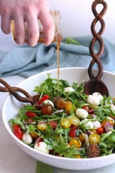 Side shot of a hand drizzling salad dressing on a bowl of arugula Caprese salad.
