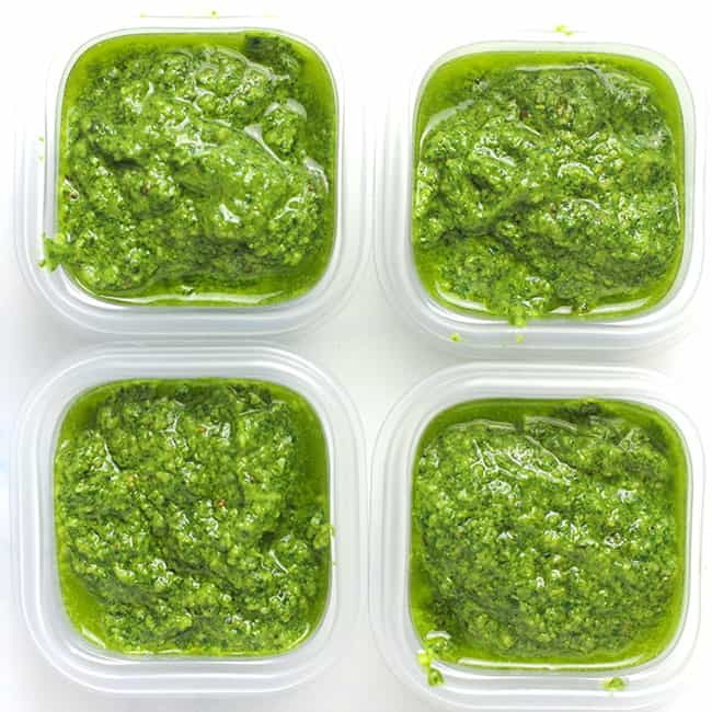 Four small containers of homemade pesto sauce for the freezer.