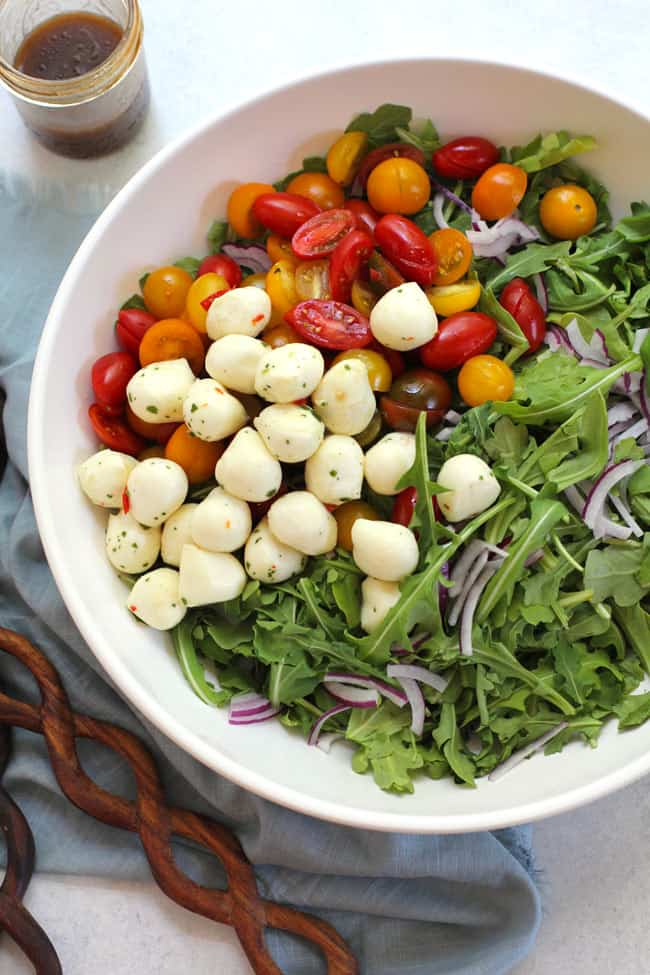 Overhead shot of a large bowl of arugula, tomatoes, mozzarella balls, with a jar of dressing.