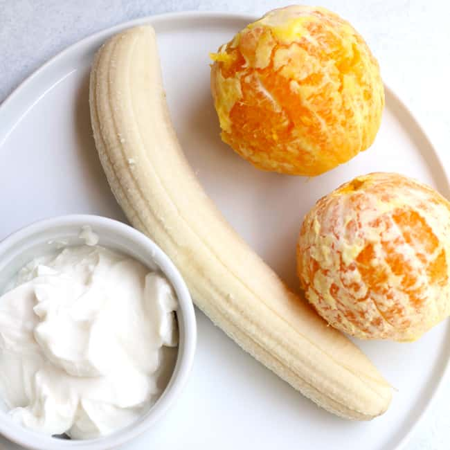 Overhead shot of a white plate with ingredients: two oranges, one banana, and some vanilla yogurt.