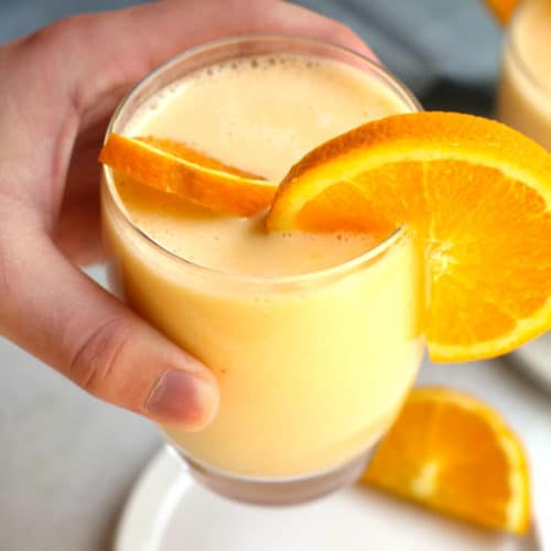 Overhead shot of a hand holding a glass of Orange Julius Smoothie, with a white plate underneath.