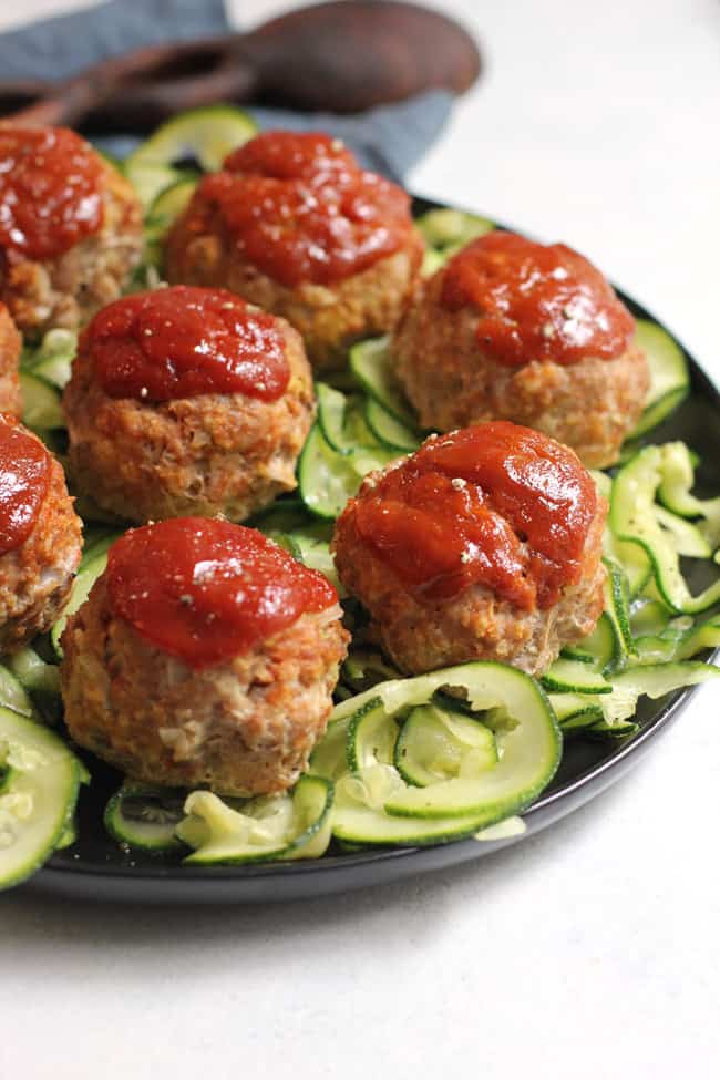 Side shot of a partial plate of turkey meatloaf muffins on a bed of zucchini noodles.