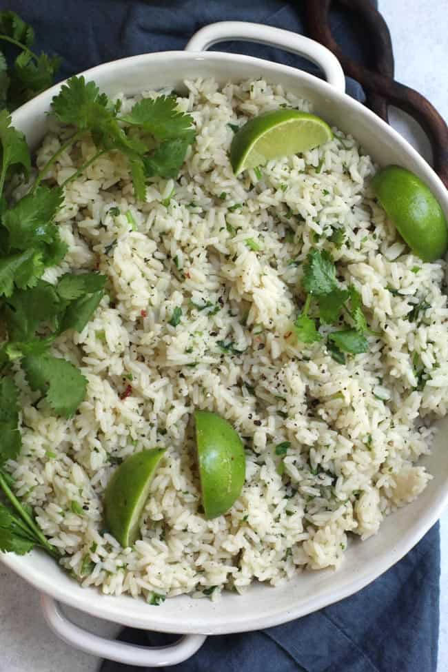 Overhead shot of white bowl with handles, full of cilantro lime rice.