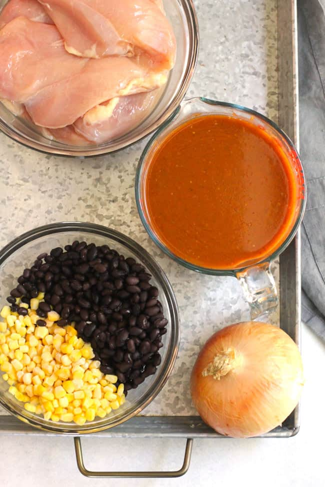 All the ingredients on a gray tray, including homemade enchilada sauce.