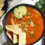Overhead shot of one black bowl filled with chicken tortilla soup, with chips and avocado, on a gray tray.