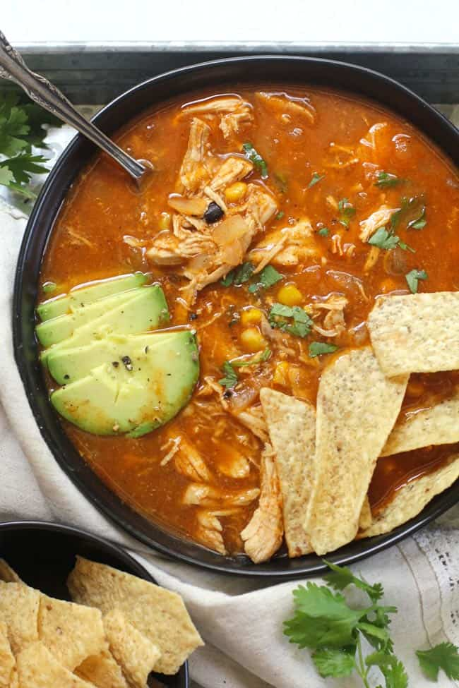 A bowl of chicken tortilla soup, with chips and a spoon.