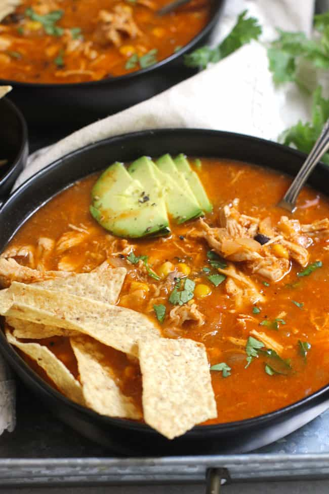Side view of one black bowl filled with chicken tortilla soup, with chips and avocado, on a gray tray.