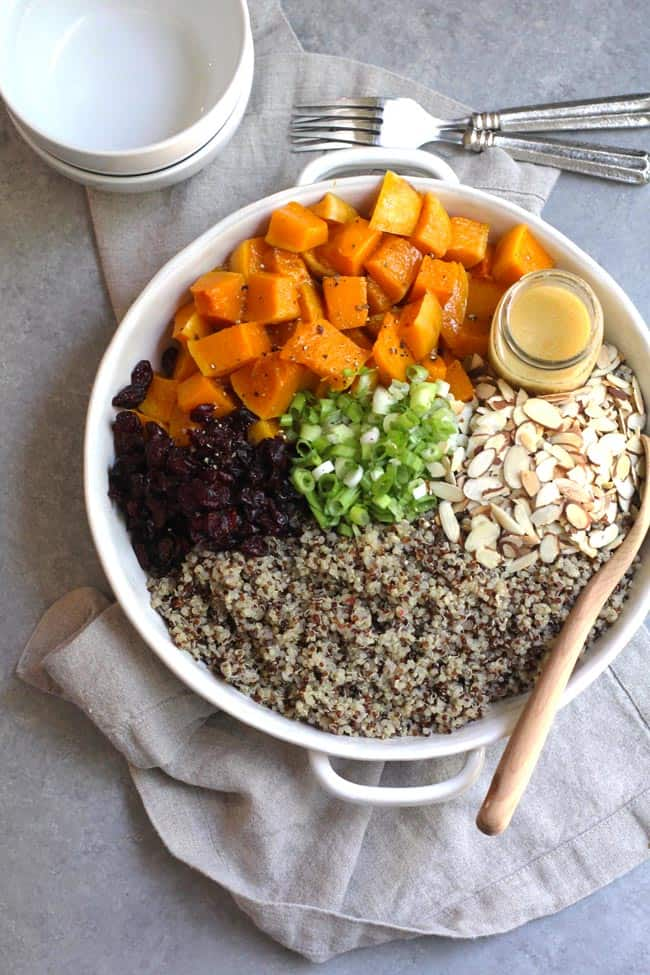 Overhead shot of a dish of squash quinoa salad, divided by ingredient, on a gray background.