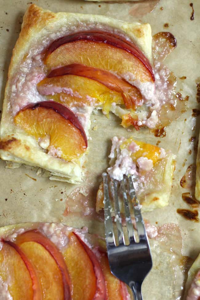 Close-up shot of a peach tartlets, with a fork removing a corner.