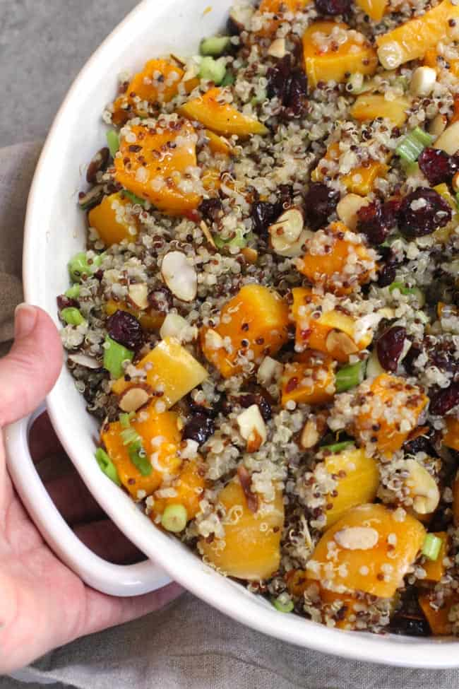 Close up of my hand holding a corner of the squash quinoa salad.