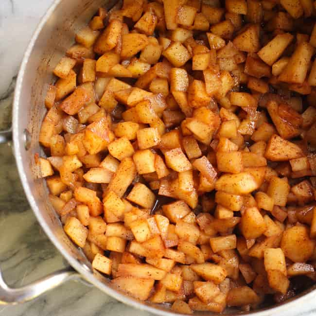 Overhead shot of a partial pan of baked, diced apples, in cinnamon and butter.