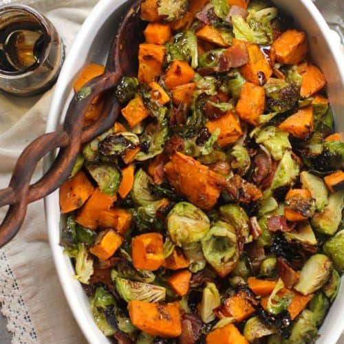 Overhead shot of a oblong white casserole dish of balsamic glazed Brussels sprouts and sweet potatoes, with a wooden spoon.