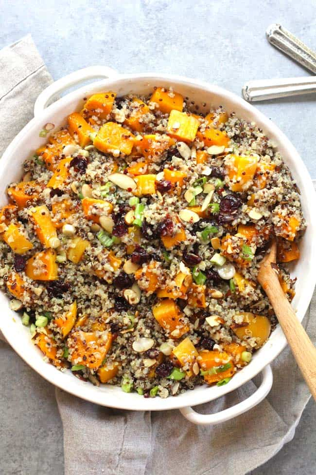 Overhead shot of a white dish of butternut squash quinoa salad, on a gray background.