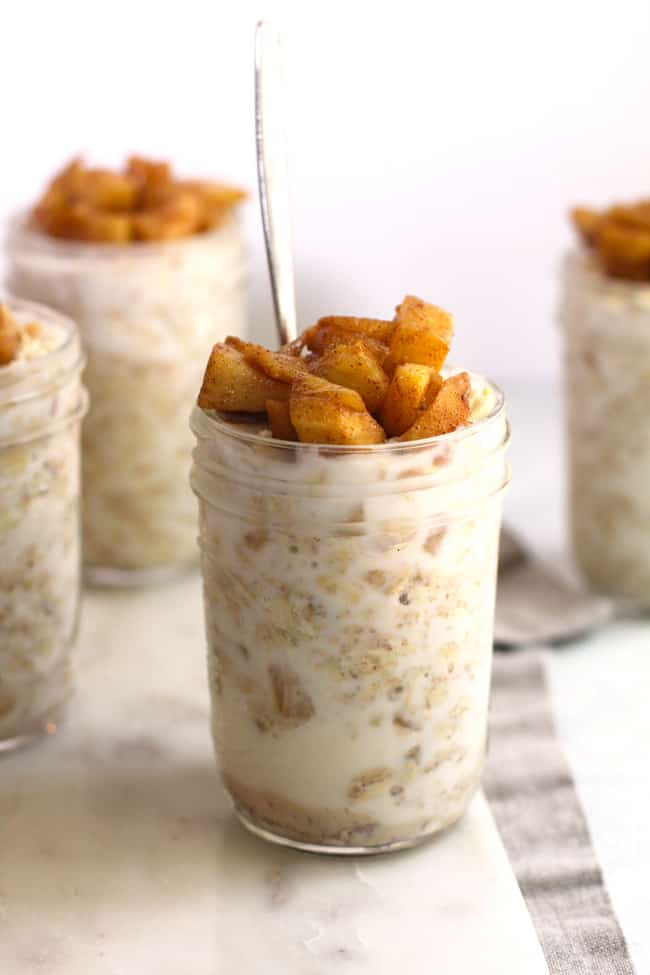 Side shot of four smaller jars of apple pie overnight oats, with one front and center.