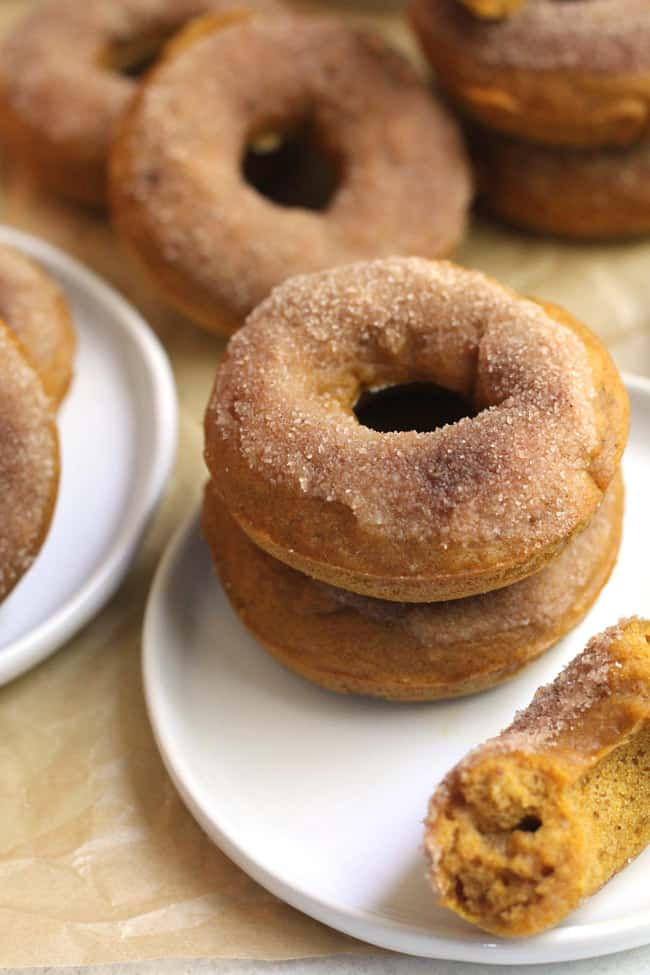 Overhead view of baked pumpkin donuts, with two stacked on a plate.