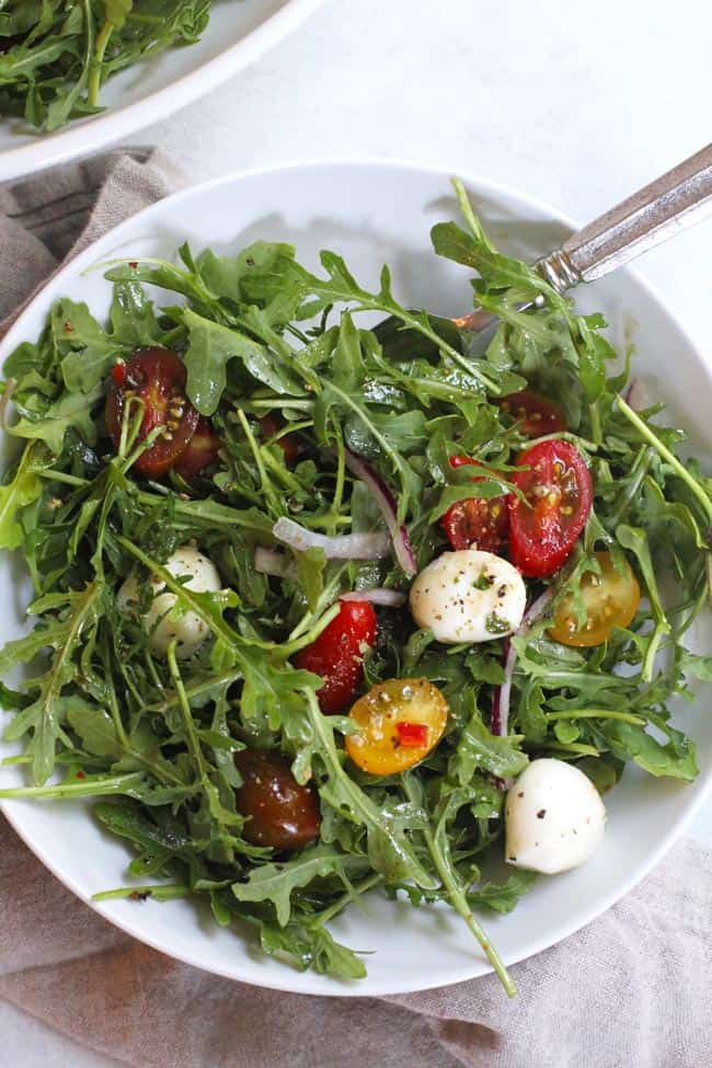 Overhead shot of a white serving bowl of arugula Caprese salad, with a fork inside.