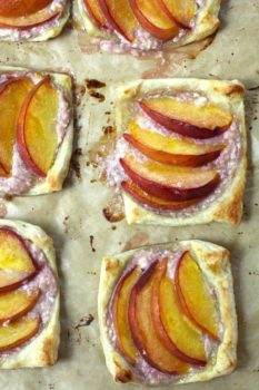 Overhead shot of a sheet pan of baked puff pastry peach tartlets, on tan parchment paper.