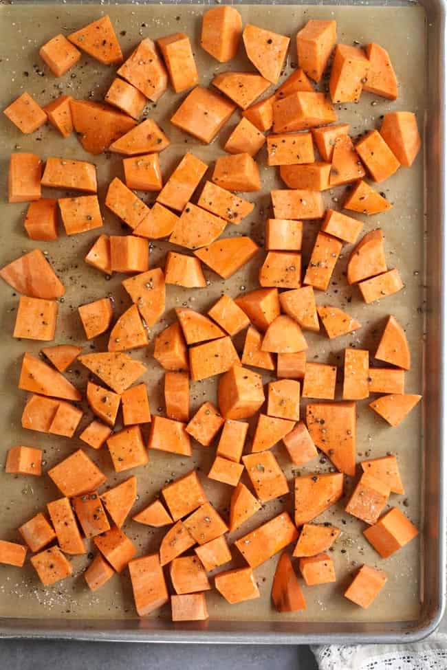 Sheet pan of chopped sweet potatoes on a baking sheet, before roasting.