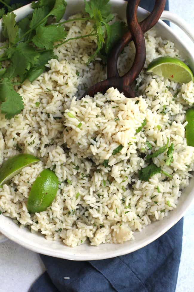 Close-up of a wooden spoon in a white bowl of cilantro lime rice.