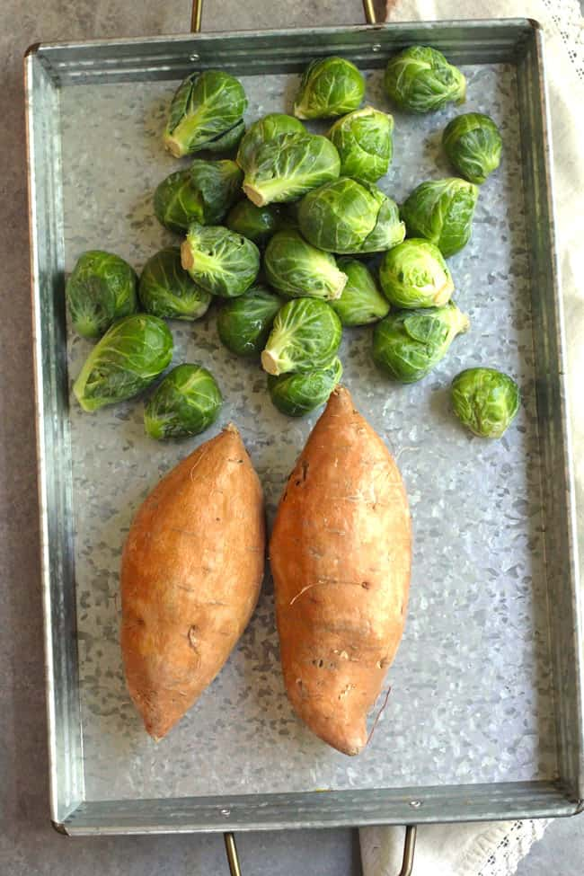 A tray of raw Brussels sprouts and two whole sweet potatoes.