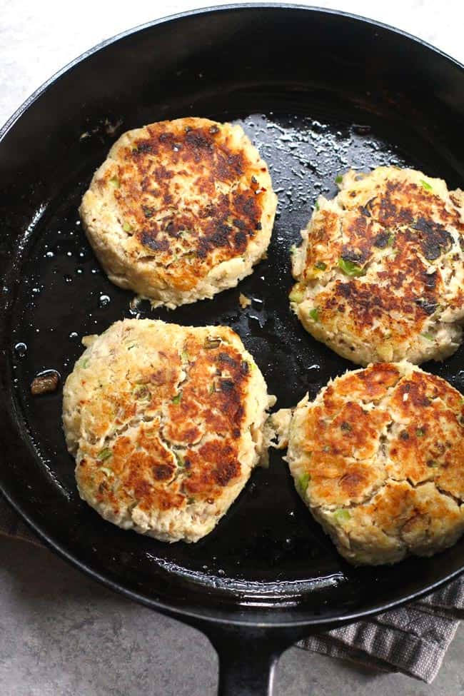 Overhead shot of four tuna patties in a cast iron skillet.